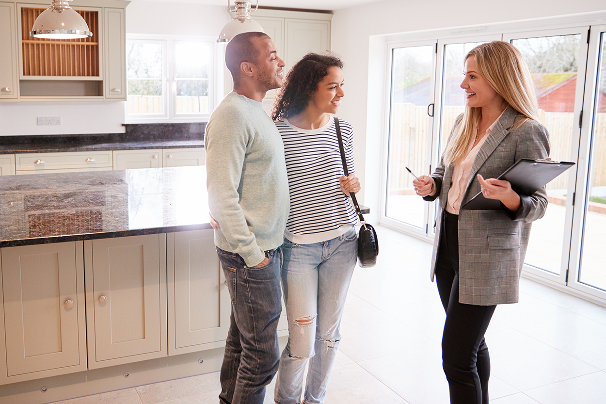 Young couple touring home with realtor