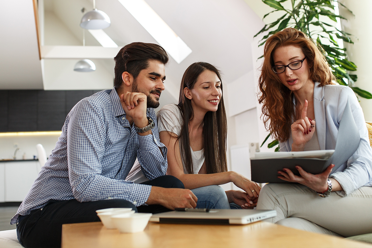 Young couple meet with realtor in living room