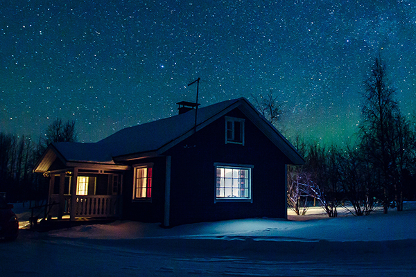 Cabin at night with starry skies and northern lights