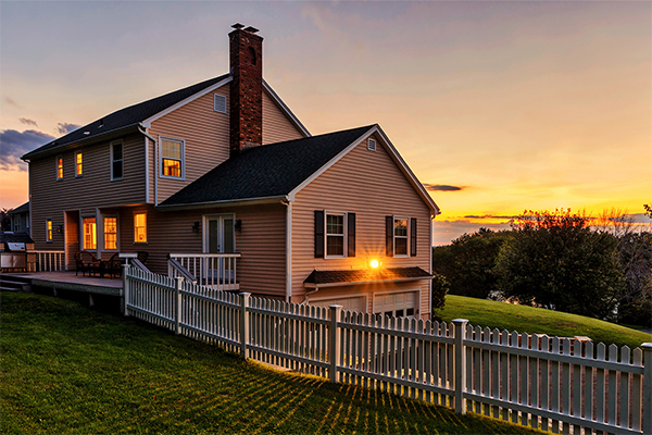 House in the country with picket fence at sunset
