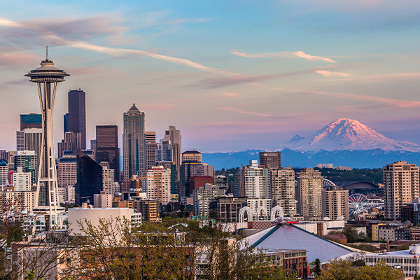 Skyline of Seattle with mountains in the background at sunset