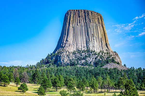 Devils tower in Wyoming with blue skies and green trees