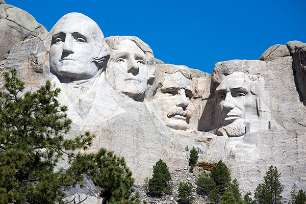Mount Rushmore with blue skies and greenery