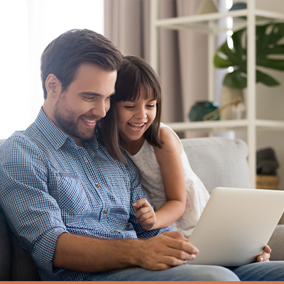 Young dad and his daughter using a laptop