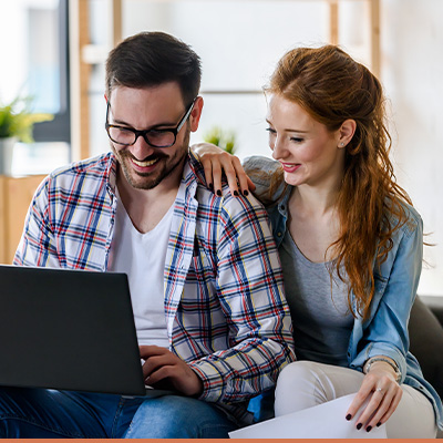 Couple smiling, researching on laptop