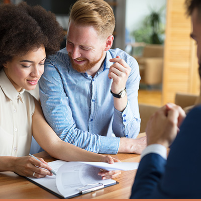 Young couple signing mortgage paperwork with realtor