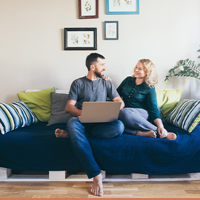 Happy young couple on couch with laptop