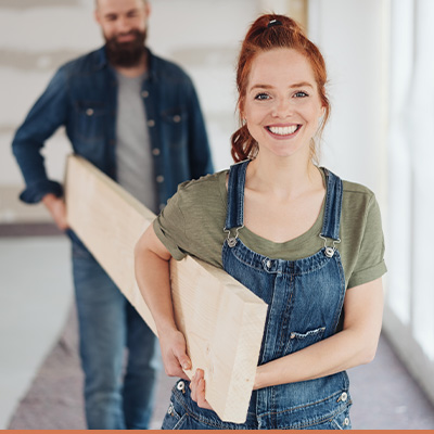 Young couple carrying hardwood during home renovation