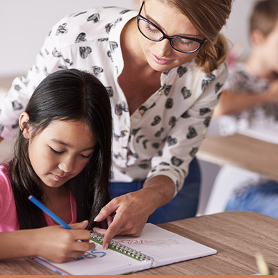 Young teacher helping child at desk