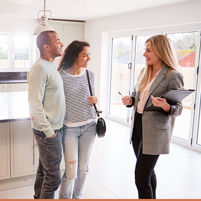 Young couple talking to realtor in kitchen