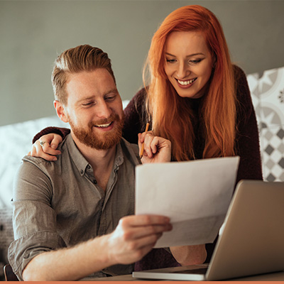 young couple smiling while reviewing paperwork