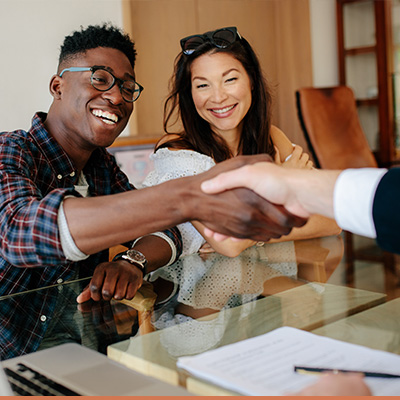 Young couple shaking hands with lender