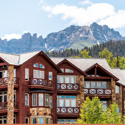 Wood and stone condos with mountains in the background
