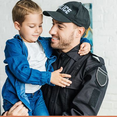 Dad in police uniform holding his young son
