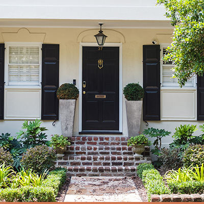 Southern front porch with brick steps and landscaped plants around