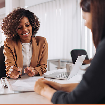 Business woman explains information to client pointing to paperwork