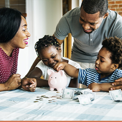 Young family saving their money in a piggy bank