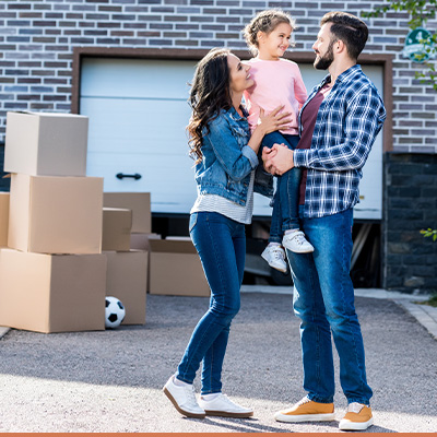 Young happy family in driveway with moving boxes around them
