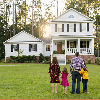 Family holding hands in front of new farm house