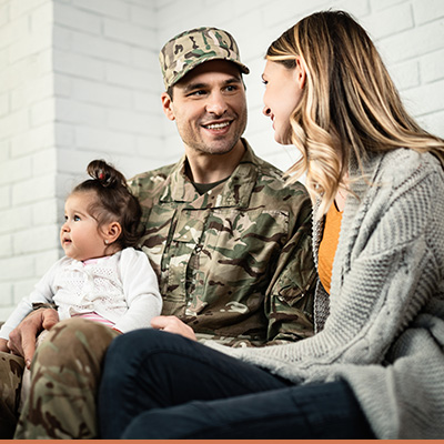 Young family with military father sitting on couch talking