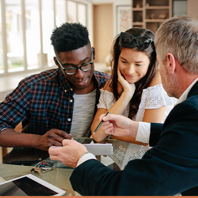 Young couple meeting with realtor learning information from paperwork
