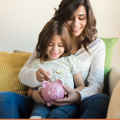 Young mom and her daughter holding piggy bank