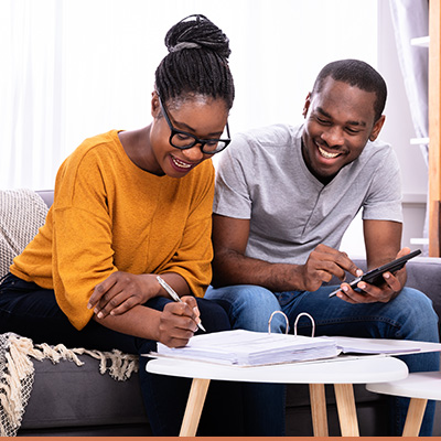 Couple sitting on couch filling out paperwork smiling