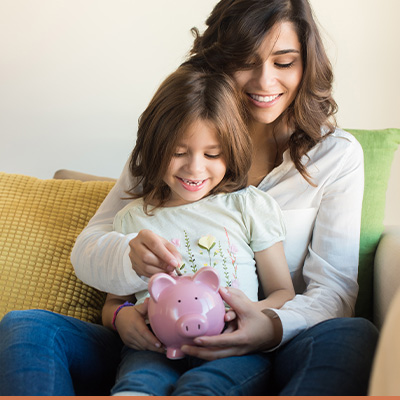 Mom with daughter saving money in piggy bank