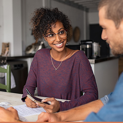 Young couple reviewing paperwork, weighing out their options