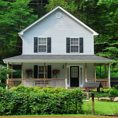 White farm house with green trees and shrubs in yard