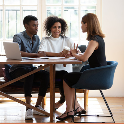 Young couple meeting with realtor at dining room table