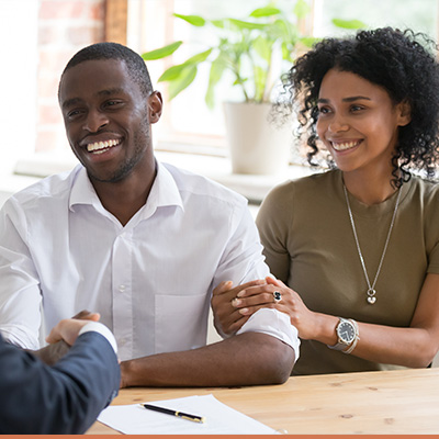 Young couple meeting with realtor shaking hands