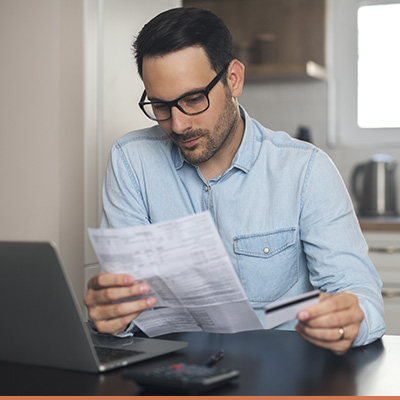Young man reviewing credit report holding credit card