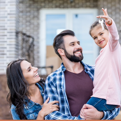 Young happy family outside new house holding the key