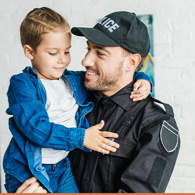 Young police father holding his son smiling