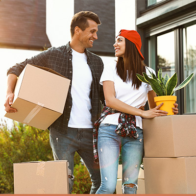Young couple outside new house carrying moving boxes