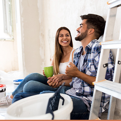 Young couple sitting down talking during a house renovation