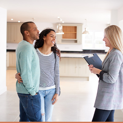 Young couple looking at a home with realtor
