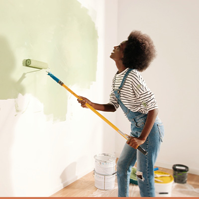 Woman painting wall in house