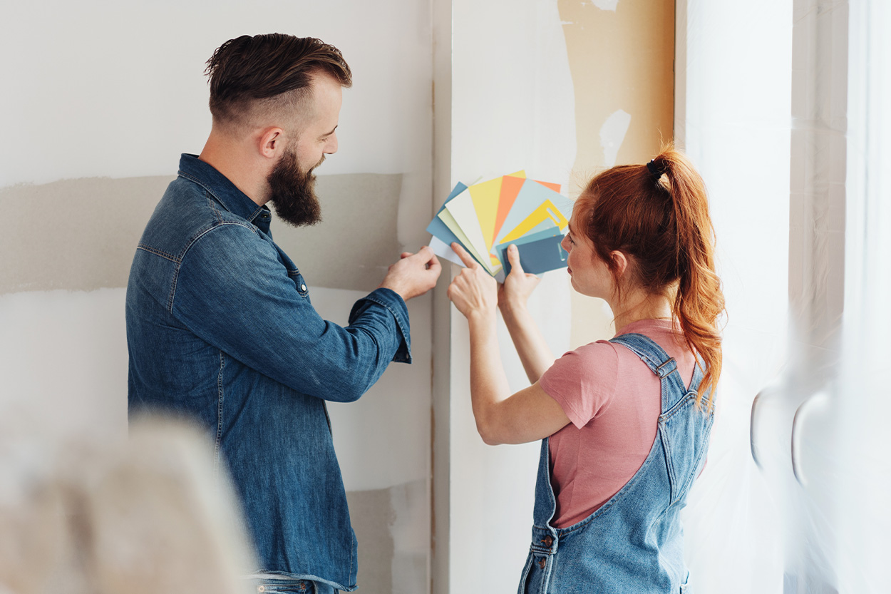Couple holding paint swatches against wall