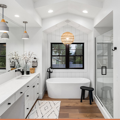 Renovated bathroom with white countertops and black hardware