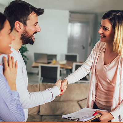 Young couple in house shaking hands with realtor
