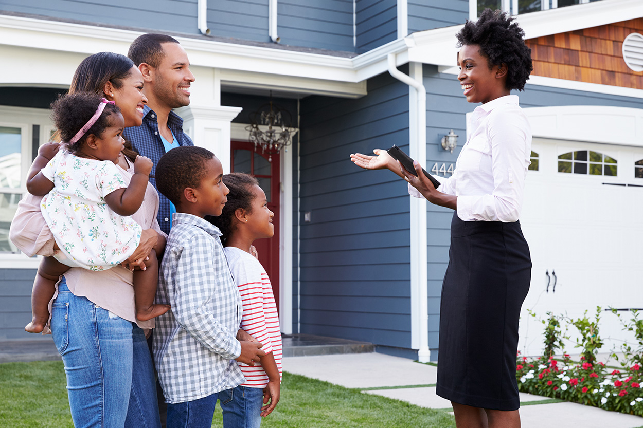 Realtor speaking with her clients outside of house