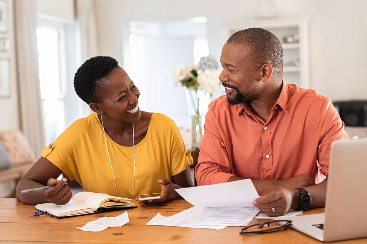 Couple at table reviewing paperwork smiling