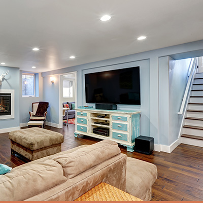 Interior finished basement with light blue walls and wood staircase