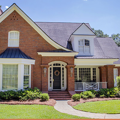 Exterior brick home with white trim and landscaped yard