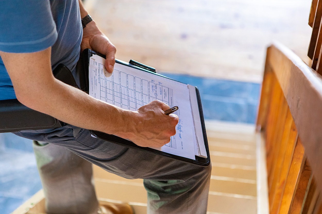 Man filling out paperwork on clipboard on stairs