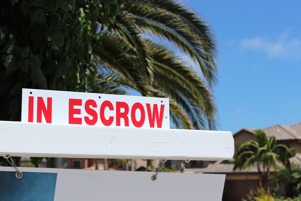 Escrow sign above for sale sign in yard