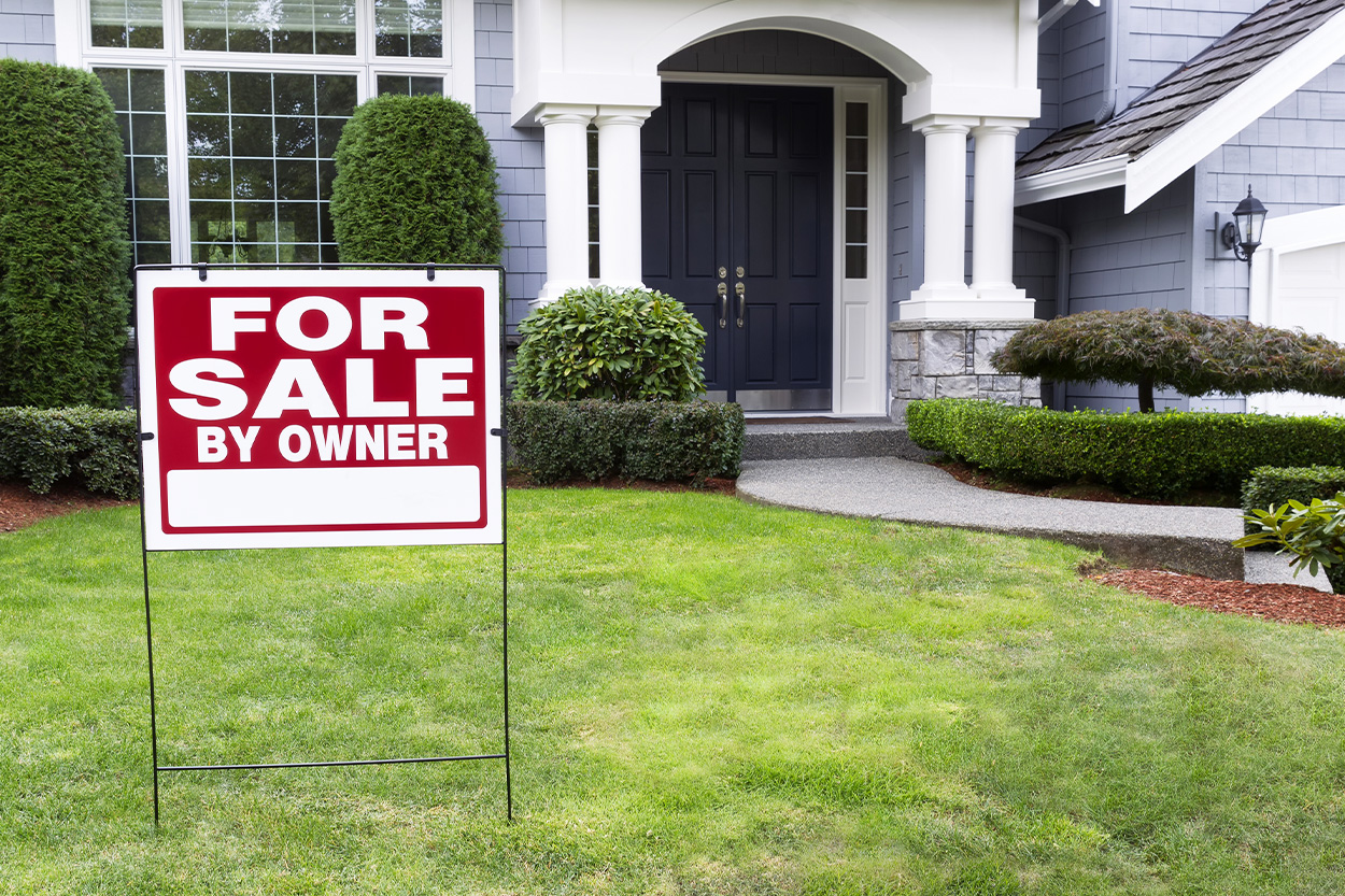 For sale by owner sign in front lawn