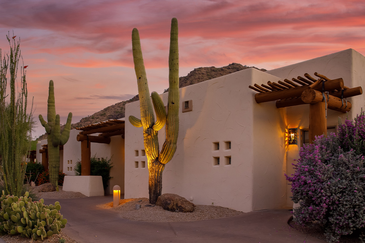 Aztec style home with cacti in yard at sunset